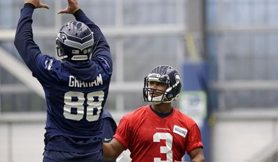 Seattle Seahawks tight end Jimmy Graham (88) goes through a catching motion as he talks with quarterback Russell Wilson during NFL football practice Thursday, June 15, 2017, in Renton, Wash. (AP Photo/Elaine Thompson)