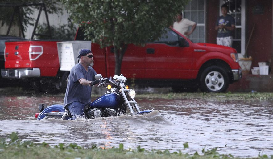 A man rides his motorcycle down Muskingum Avenue despite high levels of flooding in Odessa, Texas, Wednesday, June 14, 2017. (Jacob Ford/Odessa American via AP)