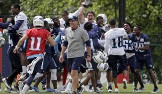 Tennessee Titans head coach Mike Mularkey walks off the field as players celebrate after beating the coaches in a high-speed punt, pass and kick competition during NFL football minicamp Thursday, June 15, 2017, in Nashville, Tenn. Since the players won, they earned a pass from the final practice of their three-day minicamp and wrapped up the offseason program a bit early. (AP Photo/Mark Humphrey)