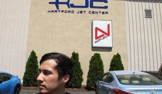 In this Wednesday, June 14, 2017 photo, Arslan Mamiliyev, who was training to become a commercial pilot at the American Flight Academy in Hartford, Conn., stands outside the building where the school was located. He and other international students are suing the school, saying they lost thousands of dollars and are being forced to leave the country after the school closed following two fatal plane crashes. Federal authorities are investigating the crashes and have seized records from the school. (AP Photo/Dave Collins)