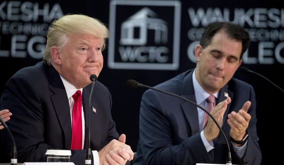 President Donald Trump accompanied by Wisconsin Gov. Scott Walker, right, speaks at a workforce development roundtable at Waukesha County Technical College in Pewaukee, Wis., Tuesday, June 13, 2017. (AP Photo/Andrew Harnik)