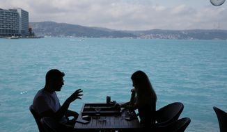 People play backgammon in a coffee shop by Istanbul's Bosphorus Strait, Wednesday, June 14, 2017. Turkish media report a significant part of the Black Sea and the Bosphorus has turned turquoise due to phytoplankton.(AP Photo/Lefteris Pitarakis)