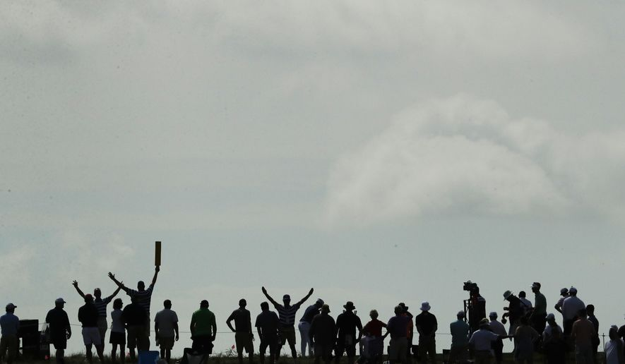 Fans watch on the fifth green during the first round of the U.S. Open golf tournament Thursday, June 15, 2017, at Erin Hills in Erin, Wis. (AP Photo/Charlie Riedel)
