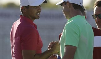 Jason Day, of Australia, shakes hands with Rory Mcilroy, of Ireland, on the 18th hole during the first round of the U.S. Open golf tournament Thursday, June 15, 2017, at Erin Hills in Erin, Wis. (AP Photo/David J. Phillip)