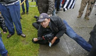 A person protesting with the conservative group Patriot Prayer, top, detains a counter-protester who had been involved in an altercation with the group before other members of the group dragged the counter-protester to Washington State Troopers, Thursday, June 15, 2017, at Evergreen State College in Olympia, Wash. (AP Photo/Ted S. Warren)