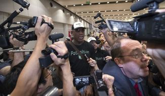 Former NBA basketball player Dennis Rodman, center, arrives at Beijing Capital International Airport in Beijing, Saturday, June 17, 2017, after a flight from Pyongyang. Rodman, vowing to come back again soon, on Saturday wrapped up a low-key and incident-free visit to the North Korean capital. (AP Photo/Mark Schiefelbein)