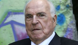The May 16, 2014 photo shows former German Chancellor Helmut Kohl in front of a piece of the Berlin Wall in Kohl's garden in Oggersheim near Ludwigshafen, southwestern Germany. (AP Photo/Michael Probst, file)