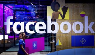 A conference worker passes a demo booth at Facebook's annual F8 developer conference, in San Jose, California, Tuesday, April 18, 2017. (AP Photo/Noah Berger) ** FILE **