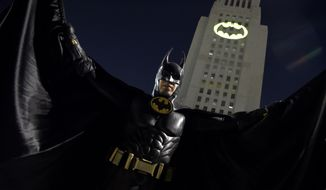 "A man poses in front of a Bat-Signal projected onto City Hall at a tribute to ""Batman"" star Adam West on Thursday, June 15, 2017, in Los Angeles. (Photo by Chris Pizzello/Invision/AP) **FILE**"