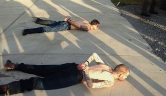 This photo provided by the Tennessee Bureau of Investigation shows the arrest of the two Georgia fugitives Donnie Rowe, top, and Ricky Dubose, bottom, in Christiana, Tenn., Thursday, June 15, 2017. The escaped inmates sought in the killings of two guards on a Georgia prison bus were captured Thursday in Tennessee after holding an elderly couple captive and leading police on a chase by car and foot, authorities said. (Tennessee Bureau of Investigation via AP)
