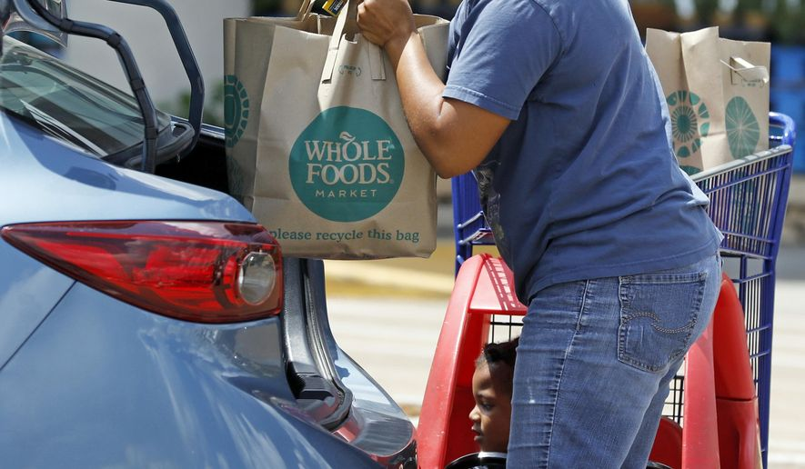 Whole Foods customer Bethany Capels, 34, of Mendenhall, Miss., loads her Whole Foods Market purchases in her car in Jackson, Miss., Friday, June 16, 2017. Amazon is buying Whole Foods Market in a deal valued at $13.7 billion, uniting the on-line giant with the grocery store chain that touts fresh organic foods. (AP Photo/Rogelio V. Solis)