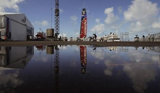 The Emirates Team New Zealand windsail is mirrored in a puddle as the team hauls out the boat in the Great Sound, Thursday, June 15, 2017, in Hamilton, Bermuda. Emirates Team New Zealand faces Oracle Team USA in the America's Cup sailing match starting June 17. (AP Photo/Gregory Bull)