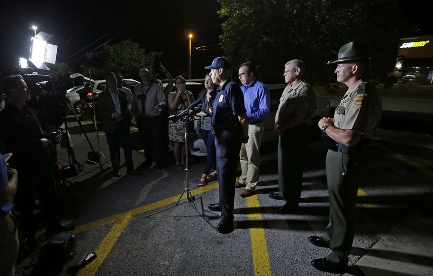 Tennessee Bureau of Investigation Director Mark Gwyn, center, speaks during a news conference held at a truck stop Thursday, June 15, 2017, in Christiana, Tenn. The two escaped inmates sought in the killings of two guards on a Georgia prison bus were captured Thursday in Tennessee after holding an elderly couple captive and leading police on a chase by car and foot, authorities said. (AP Photo/Mark Humphrey)