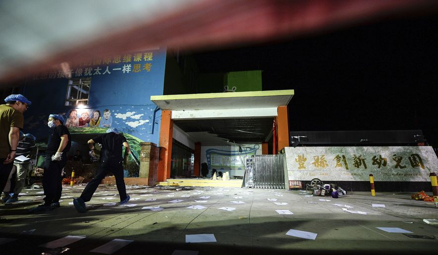 In this photo released by China's Xinhua News Agency, investigators work early Friday, June 16, 2017, at the scene of an explosion outside a kindergarten in Fengxian County in eastern China's Jiangsu Province. Several people were killed and dozens more injured in an explosion Thursday at the front gate of the kindergarten in eastern China as relatives were picking up their children at the end of the school day, local officials said. (Li Xiang/Xinhua via AP)