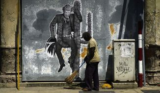 A street sweeper cleans the sidewalk under a mural painting depicting U.S. President Donald Trump, in Havana, Cuba, Friday, June 16, 2017. President Trump is en route to Miami, where he'll announce his plans for halting the flow of U.S. cash to Cuba's military and security services while maintaining diplomatic relations, in a partial reversal of the Obama administration policies. (AP Photo/Ramon Espinosa)