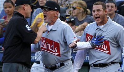 Chicago Cubs manager Joe Maddon, center, argues with umpire Jeff Kellogg, left, over a home run that was called a foul ball by Anthony Rizzo, right, who is restrained from getting into the discussion by Kyle Schwarber in the first inning of a baseball game against the Pittsburgh Pirates in Pittsburgh, Friday, June 16, 2017. Maddon was eventually eject from the game by Kellogg. Rizzo drew a walk of Pirates starting pitcher Trevor Williams. (AP Photo/Gene J. Puskar)