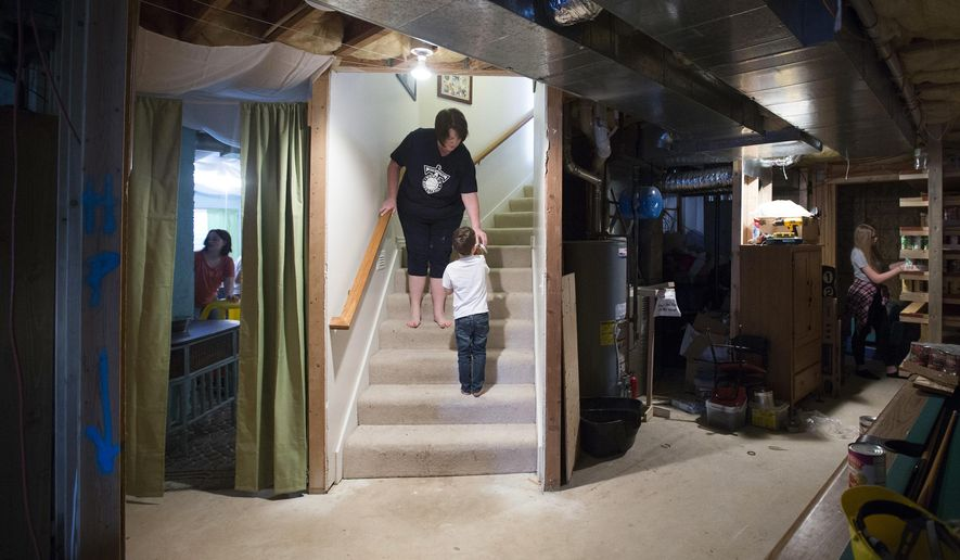 Jody Lucas, center, helps Oliver Steven with a jar of food in the family's  basement in Syracuse, Utah on Wednesday, April 5, 2017.  Jody and Nate Lucas have adopted a number of children into their family of 17.   (Briana Scroggins/Standard-Examiner via AP)