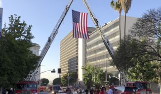 A flag is placed over Temple Street in downtown Los Angeles,during the funeral for fallen Firefighter Kelly Wong at the Cathedral Of Our Lady Of Angels, Friday,  June 16, 2017 in Los Angeles. The 29-year-old Wong fell from the ladder on June 3 and died two days later. (Mark Boster /Los Angeles Times via AP)