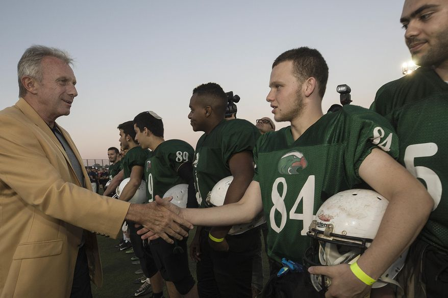 In this Thursday, June 15, 2017 photo, former NFL player Joe Montana shakes hands with an Israeli football player in Ramat Hasharon, near Tel Aviv, Israel. 18 members of the Pro Football Hall of Fame who arrived for a weeklong visit to meet some of the 2,000 active players in Israel's various leagues organized by New England Patriots owner Robert Kraft, who has been sponsoring the sport in Israel since it was launched in 1999.(AP Photo/Tsafrir Abayov)