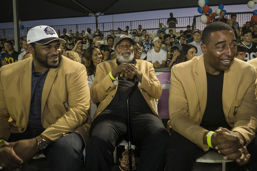 In this Thursday, June 15, 2017 photo, former NFL players, from left, Jerome Bettis, Jim Brown and Cris Carter attend a football game in Ramat Hasharon, near Tel Aviv, Israel. 18 members of the Pro Football Hall of Fame who arrived for a weeklong visit to meet some of the 2,000 active players in Israel's various leagues organized by New England Patriots owner Robert Kraft, who has been sponsoring the sport in Israel since it was launched in 1999.(AP Photo/Tsafrir Abayov)