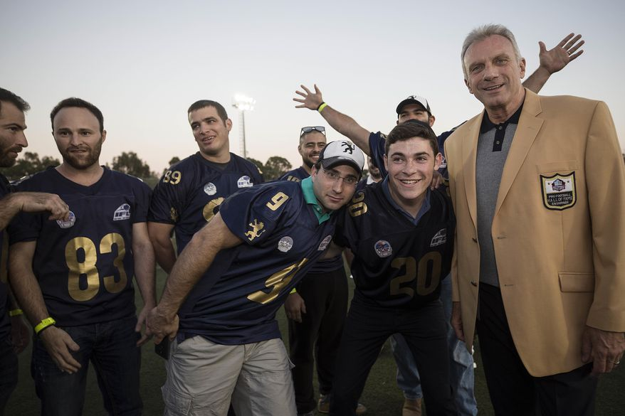 In this Thursday, June 15, 2017 photo, former NFL player Joe Montana poses with Israeli football players in Ramat Hasharon, near Tel Aviv, Israel. 18 members of the Pro Football Hall of Fame who arrived for a weeklong visit to meet some of the 2,000 active players in Israel's various leagues organized by New England Patriots owner Robert Kraft, who has been sponsoring the sport in Israel since it was launched in 1999.(AP Photo/Tsafrir Abayov)