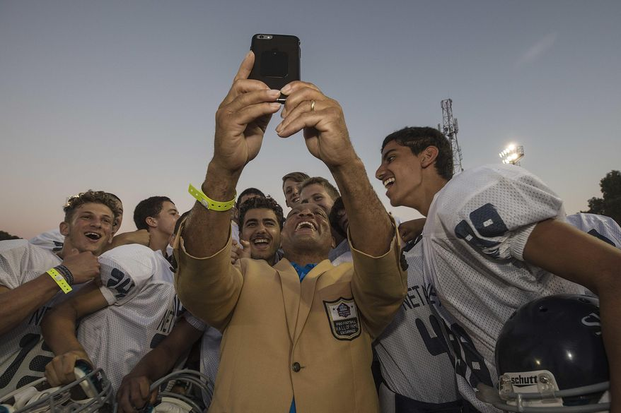 In this Thursday, June 15, 2017 photo, former NFL player Aeneas Williams takes selfie with an Israeli football player in Ramat Hasharon, near Tel Aviv, Israel. 18 members of the Pro Football Hall of Fame who arrived for a weeklong visit to meet some of the 2,000 active players in Israel's various leagues organized by New England Patriots owner Robert Kraft, who has been sponsoring the sport in Israel since it was launched in 1999.(AP Photo/Tsafrir Abayov)