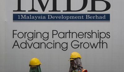 FILE - In this May 14, 2015 file photo, construction workers chat in front of a billboard for state investment fund 1 Malaysia Development Berhad (1MDB) at the fund's flagship Tun Razak Exchange development in Kuala Lumpur, Malaysia. The U.S. Justice Department is seeking to recover $540 million in assets, including penthouse apartments, paintings by Vincent Van Gogh and a yacht known as the Equanimity, that it says were stolen from Malaysia's troubled sovereign wealth fund, prompting objections from Malaysian officials who said Friday, June 16, 2017 there was no evidence of such crimes. (AP Photo/Joshua Paul, File)