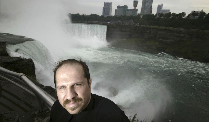 FILE- In this Aug. 13, 2004, file photo, Kirk Jones poses for a photo at Terrapin Point on the American side of Horseshoe Falls in Niagara Falls State Park, N.Y. Jones, who survived a plunge over Niagara Falls without protection in 2003 has died after he went over again, this time inside an inflatable ball.Police told the Syracuse Post-Standard that the body of the 53-year-old was found in the Niagara River by the U.S. Coast Guard on June 2, 2017. (Chip Somodevilla/Detroit Free Press via AP, File)