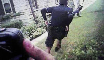This image taken Wednesday, June 14, 2017, from a screen during the trial of Milwaukee police officer Dominique Heaggan-Brown in Milwaukee shows Milwaukee Police Department body camera video of Heaggan-Brown, center, running behind 23-year-old Sylville Smith, right, after a routine traffic stop on Aug. 23, 2016. The dramatic footage prompted the Smith's relatives to leave the courtroom in tears after seeing the brief foot chase that quickly turned fatal. (Milwaukee Police Department/Milwaukee Journal-Sentinel via AP, Pool)