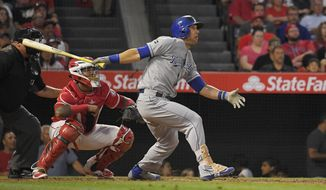 Kansas City Royals' Alex Gordon watches a solo home run in front of Los Angeles Angels catcher Martin Maldonado, center, and home plate umpire Fieldin Culbreth during the fourth inning of a baseball game, Thursday, June 15, 2017, in Anaheim, Calif. (AP Photo/Mark J. Terrill)