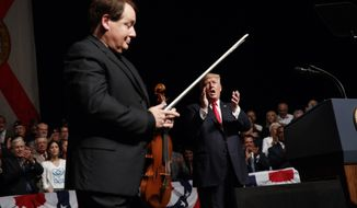 President Donald Trump cheers Cuban born violinist Luis Haza after the playing of the national anthem during a speech on Cuba policy, Friday, June 16, 2017, in Miami. (AP Photo/Evan Vucci)