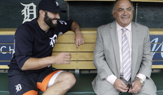In this Friday, May 19, 2017 photo, Detroit Tigers' Alex Avila, left, shares a laugh with his father, general manager Al Avila during an interview in the dugout in Detroit. Al strives to strike a balance between business and personal with his son, Alex, who plays catcher for the team. The Avilas are one of many father-son duos in sports around the world spending time together on a daily basis. (AP Photo/Carlos Osorio)