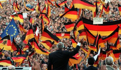 FILE - In this Feb. 20, 1990 file photo the West-German Chancellor Helmut Kohl is framed by German flags as he waves to spectators during a campaign rally in Erfurt, then still GDR. Helmut Kohl died June 16, 2017. (Heinz Wieseler/dpa via AP)