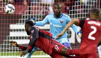 D.C. United goalkeeper Bill Hamid (28) keeps his eyes on the ball as Toronto FC forward Jozy Altidore (17) makes a diving header during first half MLS soccer action in Toronto, Saturday, June 17, 2017. (Frank Gunn/The Canadian Press via AP) **FILE**