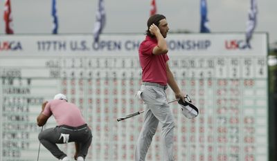 Tommy Fleetwood, of England, reacts after a bogey on the 18th hole during the third round of the U.S. Open golf tournament Saturday, June 17, 2017, at Erin Hills in Erin, Wis. (AP Photo/David J. Phillip)