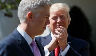 President Donald Trump applauds new Supreme Court Justice Neil Gorsuch during a public swearing-in ceremony for Gorsuch in the Rose Garden of the White House in Washington, Monday, April 10, 2017. (Associated Press)