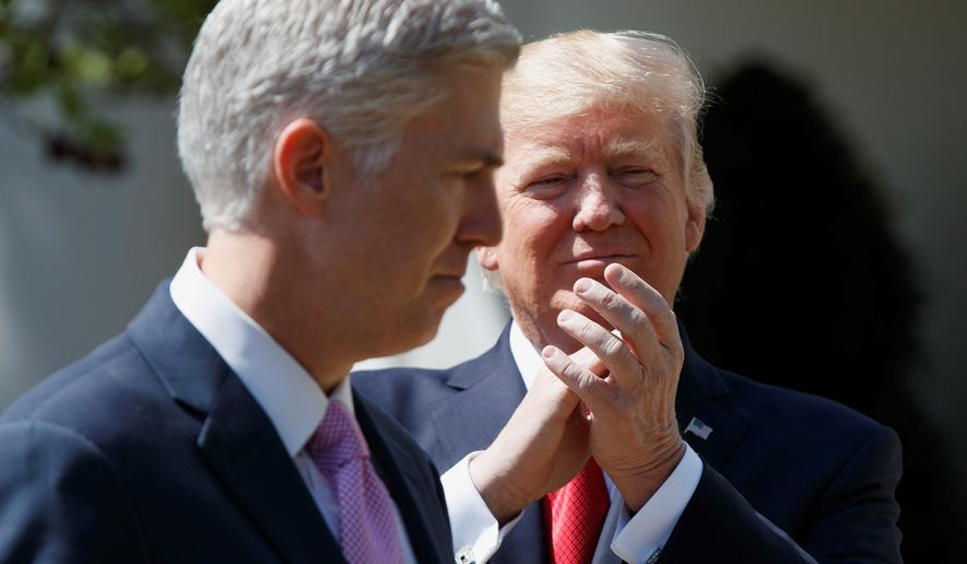 President Donald Trump applauds new Supreme Court Justice Neil Gorsuch during a public swearing-in ceremony for Gorsuch in the Rose Garden of the White House in Washington on April 10, 2017. (Associated Press) **FILE**
