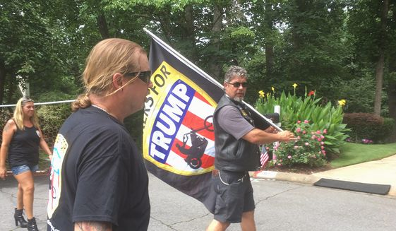 Bikers for Trump canvassed a suburban Atlanta neighborhood this weekend on behalf of a Republican Karen Handel in a hard-fought runoff race against Democrat Jon Ossoff. Chris Cox, founder of Bikers for Trump, carried the group's flag from door to door. (Seth McLaughlin/The Washington Times)