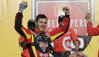 Kyle Larson raises his arms after exiting his car after winning a NASCAR Sprint Cup series auto race, Sunday, June 18, 2017, in Brooklyn, Mich. (AP Photo/Carlos Osorio)