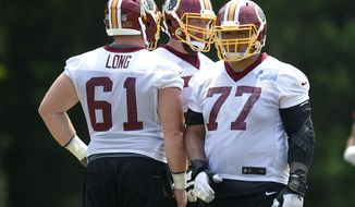 Washington Redskins guard Shawn Lauvao (77) looks on next to center Spencer Long (61) during an NFL football team practice, Wednesday, June 14, 2017, in Ashburn, Va. (AP Photo/Nick Wass)