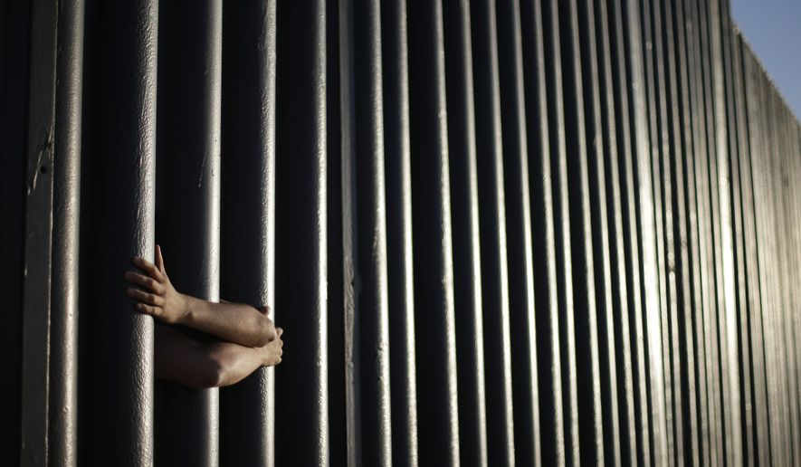 FILE - In this June 13, 2013, file photo, hands from Daniel Zambrano of Tijuana, Mexico, hold on to the bars that make up the border wall separating the U.S. and Mexico as the border meets the Pacific Ocean in San Diego. The state legislature is debating more than a dozen bills, sponsored by Democrats, to resist President Donald Trump's immigration agenda, particularly his promises to increase deportations and build a wall along the U.S.-Mexico border. (AP Photo/Gregory Bull, File)