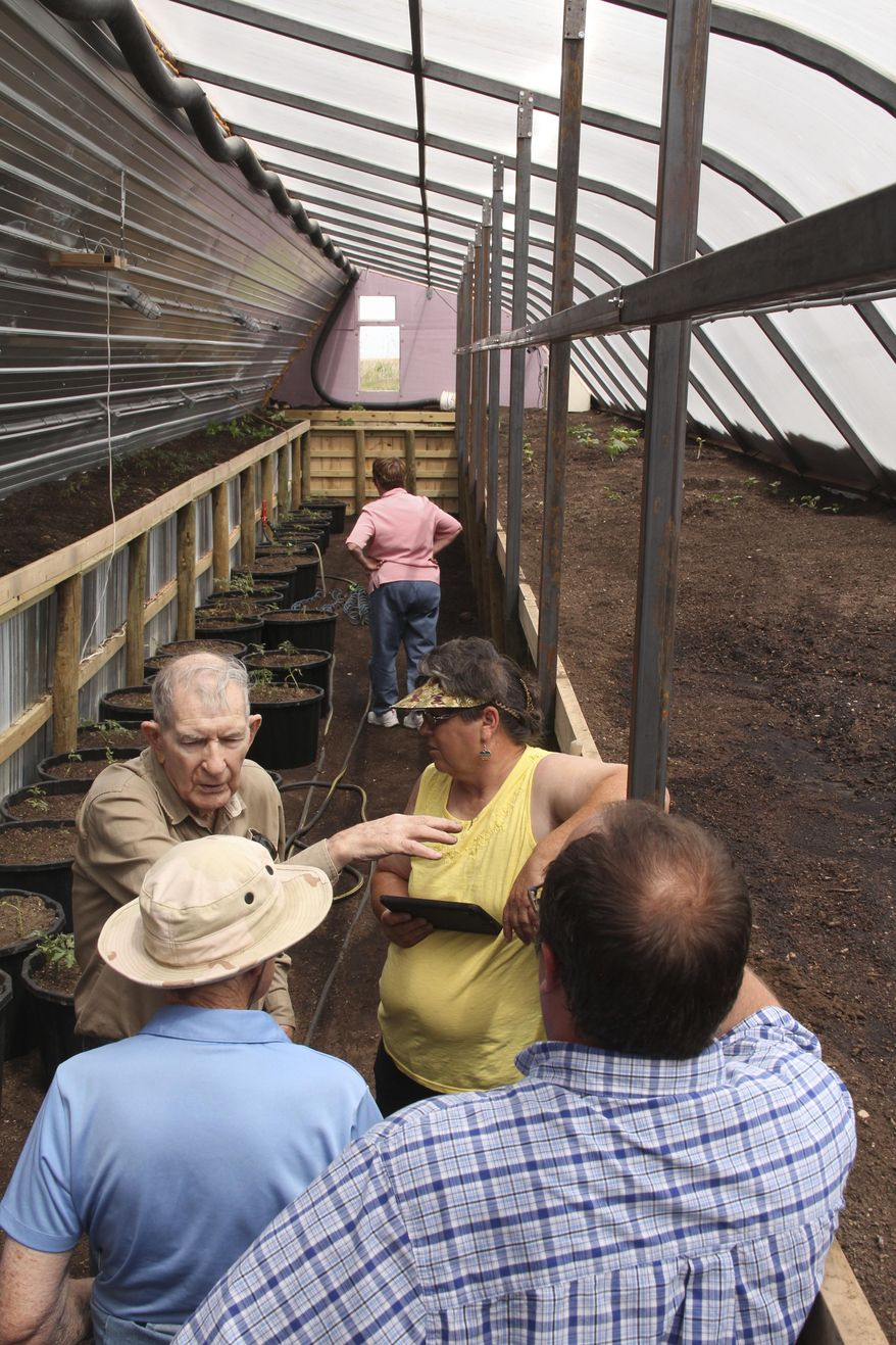 In this June 9, 2017 photo, members of the Nebraska Master Gardener Program get the opportunity to explore one of Russ Finch's newer greenhouses outside of Alliance, Neb. Finch has created greenhouses that run on geothermal heat. Geothermal heat produces heat from the ground through a singular heat source that dispenses heat through a tubing system.  He began selling his geothermal greenhouses with his business Greenhouse in the Snow about three years ago.  (Torri Brumbaugh/The Star-Herald via AP)