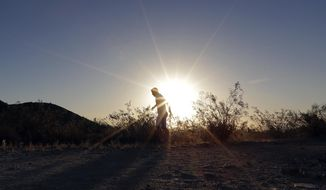In this June 16, 2017, file photo, a man runs through section of South Mountain Park at sunrise to avoid the excessive heat in Phoenix. (AP Photo/Matt York, File)
