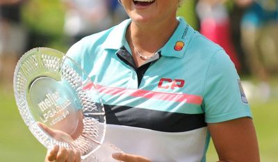 Brooke Henderson, of Canada, holds the trophy after winning the Meijer LPGA Classic golf tournament at Blythefield Country Club. Sunday, June 18, 2017, in Grand Rapids, Mich.. (Cory Olsen/The Grand Rapids Press via AP)