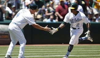 Oakland Athletics' Khris Davis (2) is congratulated by third base coach Chip Hale (4) after hitting a two run home run against the New York Yankees during the third inning of a baseball game on Sunday, June 18, 2017 in Oakland, Calif. (AP Photo/Tony Avelar)