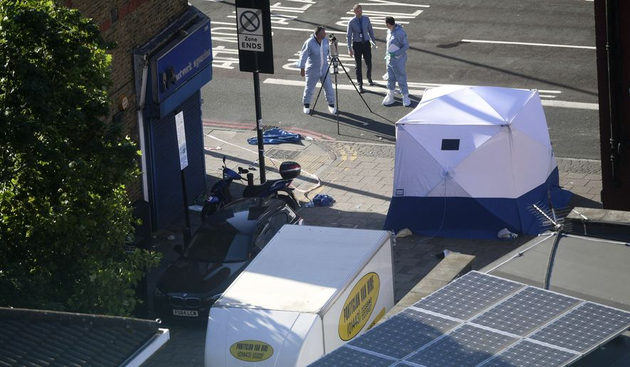 A forensic tent stands next to a van at Finsbury Park in north London after the vehicle struck pedestrians Monday, June 19, 2017. Police said a man who was driving the car has been arrested and taken to a hospital as a precaution. (Victoria Jones/PA via AP)