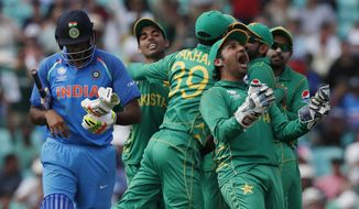 Pakistan's captain Sarfraz Ahmed, right, celebrates the dismissal of India's Ravichandran Ashwin, left, during the ICC Champions Trophy final at The Oval in London, Sunday, June 18, 2017. Embarrassed by India in its opening match, Pakistan turned the tables on its archrival to win their Champions Trophy final by a crushing 180 runs. (AP Photo/Kirsty Wigglesworth)