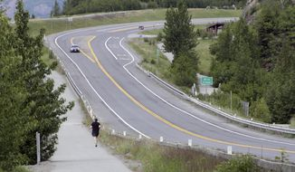 A jogger runs across the Sterling Highway from the Bird Creek access point, near a trail head that's closed on Monday, June 19, 2017, after a fatal bear mauling at Bird Ridge Trail in Anchorage, Alaska. Authorities say a black bear killed a 16-year-old runner while he was competing in an Alaska race on Sunday. (AP Photo/Mark Thiessen)