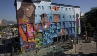 """A giant graffiti titled """"Contos"""" or """"Tales"""", created by 19-year-old Luna Buschinelli, covers an exterior of the Rivadavia Correa municipal school, in Rio de Janeiro, Brazil, Monday, June 19, 2017. Buschinelli hopes to break a Guinness World Record as the largest graffiti made by a woman. (AP Photo/Silvia Izquierdo)"""