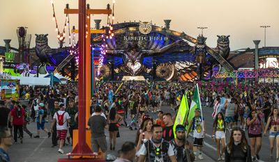 A crowd arrives on the midway during the opening night of the Electric Daisy Carnival at the Las Vegas Motor Speedway in Las Vegas on Friday, June 16, 2017.  Organizers of the largest music festival in North America are reminding attendees to report any suspicious activity they might witness during the event, less than a month after a deadly terrorist attack struck a concert in England.  (L.E. Baskow/Las Vegas Sun via AP)